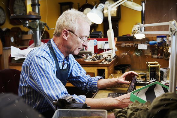 A clock repairer, a craftsman in his workshop using a laptop. - Stock Photo - Images