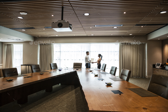 Businesswoman and man meeting in a large conference room. - Stock Photo - Images