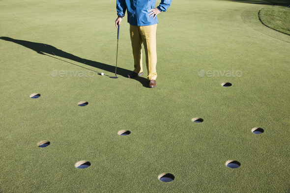 A golfer with way too many choices in possible putts on the greeen of a golf course. - Stock Photo - Images