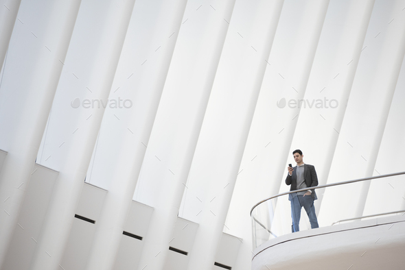 A person standing alone in an atrium by a railing on a balcony. - Stock Photo - Images