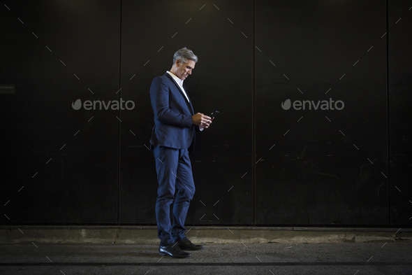A man in a suit standing in shadow on a city street, looking at his smart phone, texting or - Stock Photo - Images