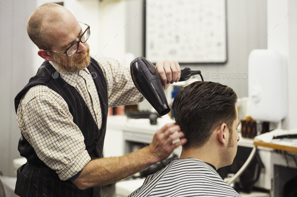 A customer sitting in the barber's chair, having his hair blow dried by a hairdresser and barber. - Stock Photo - Images