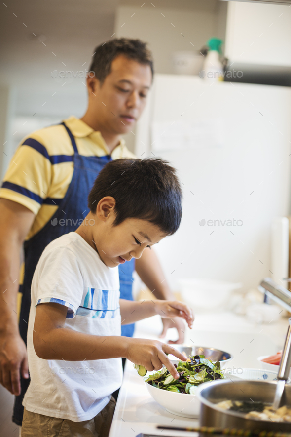 Family home. A man in a blue apron preparing a meal with his son. - Stock Photo - Images