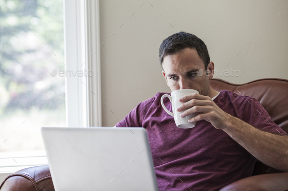 Caucasian business man using a laptop for work at home in a chair. - Stock Photo - Images