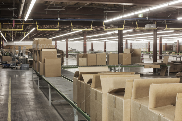 Interior view of a large distriubiton warehouse showing a mototized converyor system to move - Stock Photo - Images