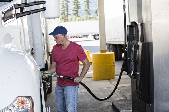 Caucasian man truck driver putting diesel fuel in his truck at a truck stop. - Stock Photo - Images