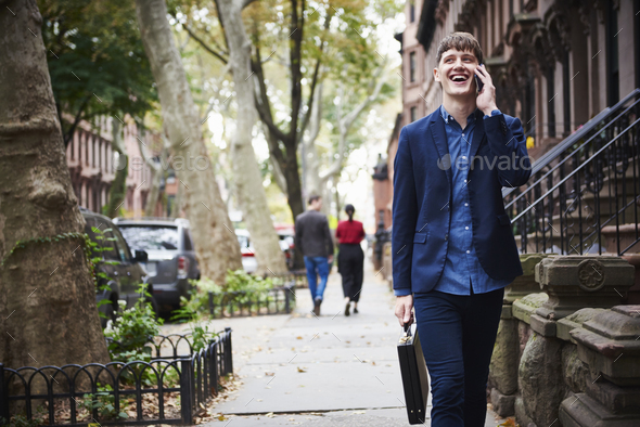 A young man walking along a city street holding a briefcase with a cellphone to his ear, - Stock Photo - Images