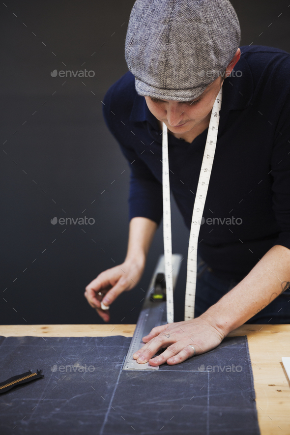 A man measuring up and marking with tailor's chalk, a piece of grey fabric using a metal ruler. - Stock Photo - Images