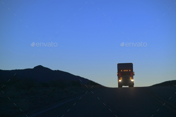 Kenworth W900 Class 8 truck shilouetted while coming over a hill on the highway. - Stock Photo - Images