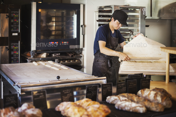 Man working in a bakery, preparing large tray with dough for rolls, oven in the background. - Stock Photo - Images