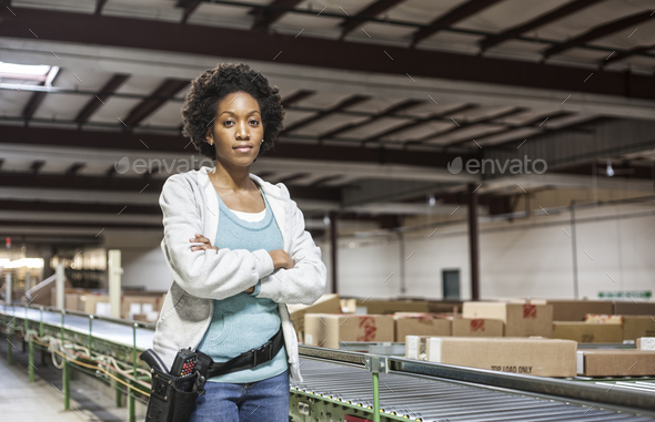 Portrait of an African American female warehouse worker in a large distribution warehouse with - Stock Photo - Images