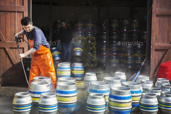 Man working in a brewery, cleaning metal beer kegs with a high pressure washer. - Stock Photo - Images