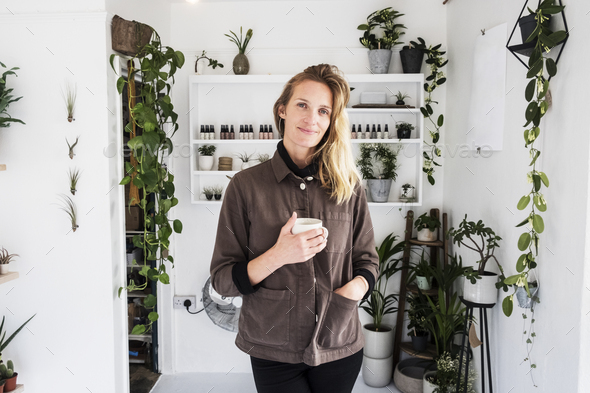 Female owner of plant shop smiling at camera, a selection of plants on wooden shelves. - Stock Photo - Images