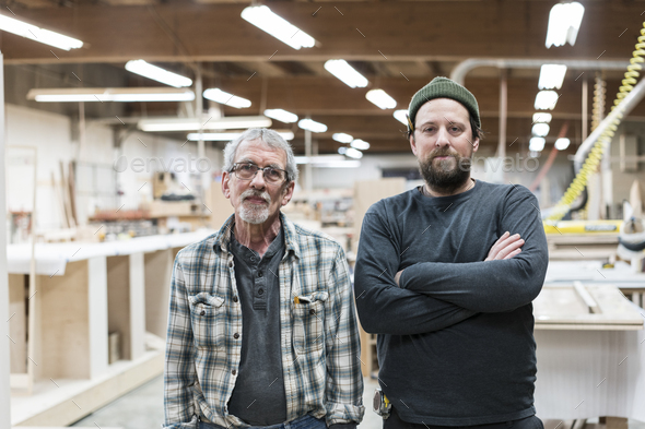 Portrait of two Caucasian carpenters in a large woodworking factory. - Stock Photo - Images