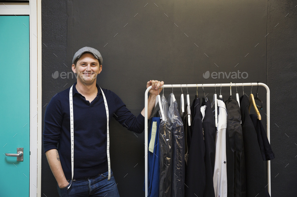 A tailor standing by a clothes rail in his workshop. - Stock Photo - Images