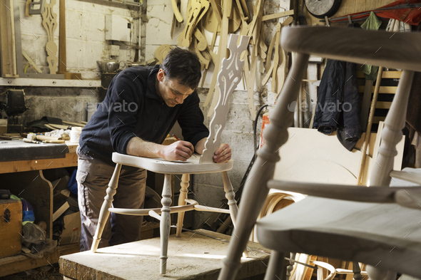 Man standing in a carpentry workshop, working on a wooden chair. - Stock Photo - Images