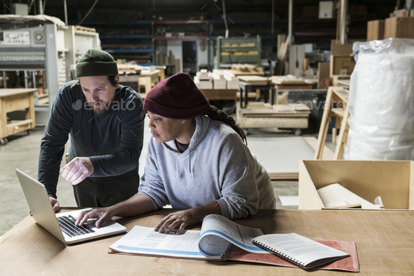 A Caucasian male carpenter and a Black female carpenter working on a laptop computer after work - Stock Photo - Images