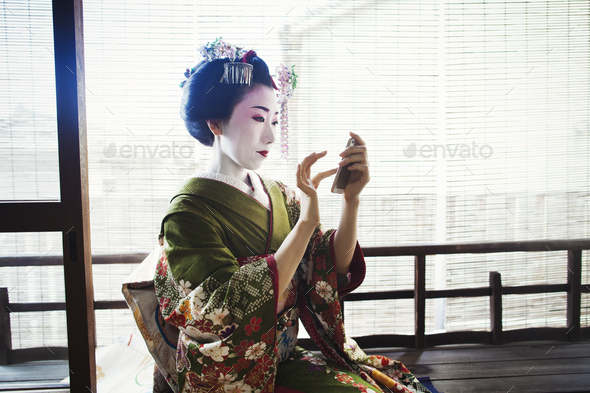 A woman dressed in the traeditional geisha style, wearing a kimono and obi, with an elaborate - Stock Photo - Images