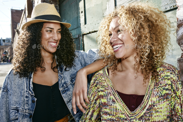 Portrait of two smiling young women with long curly black and blond hair, looking at each other. - Stock Photo - Images