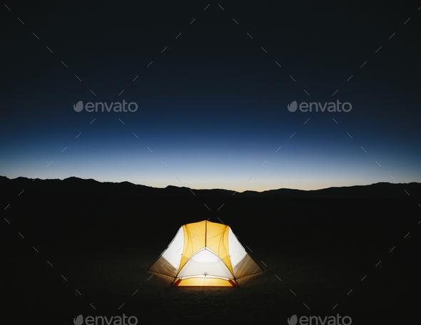 Illuminated camping tent in vast desert at dusk, Black Rock Desert, Nevada - Stock Photo - Images