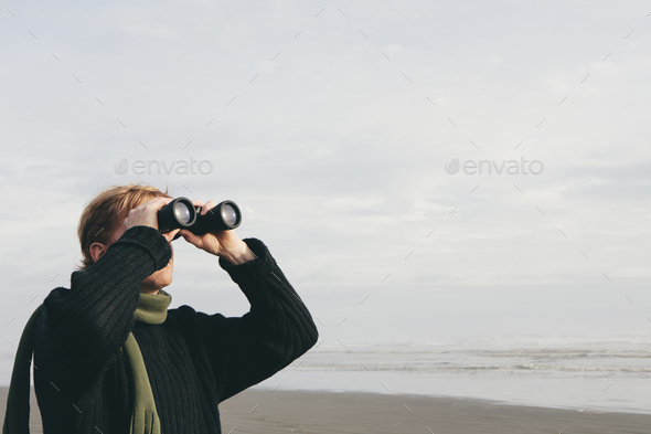 Middle aged man standing on a beach, looking through binoculars at Seabrook, Washington, USA. - Stock Photo - Images