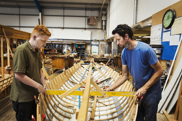Two men in a boat-builder's workshop, working together on a wooden boat hull. - Stock Photo - Images