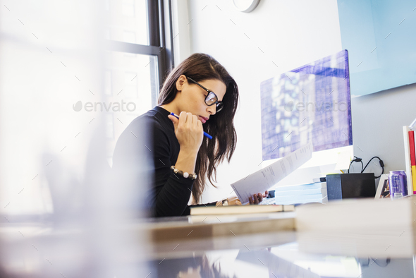 A young woman sitting at a desk in an office looking at paperwork. - Stock Photo - Images