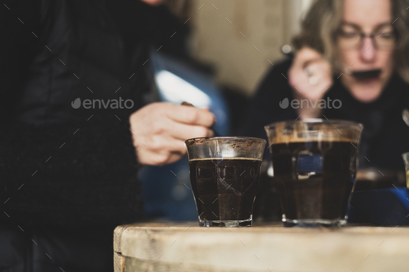 Close up of two glasses with coffee standing on wooden table, people in background. - Stock Photo - Images