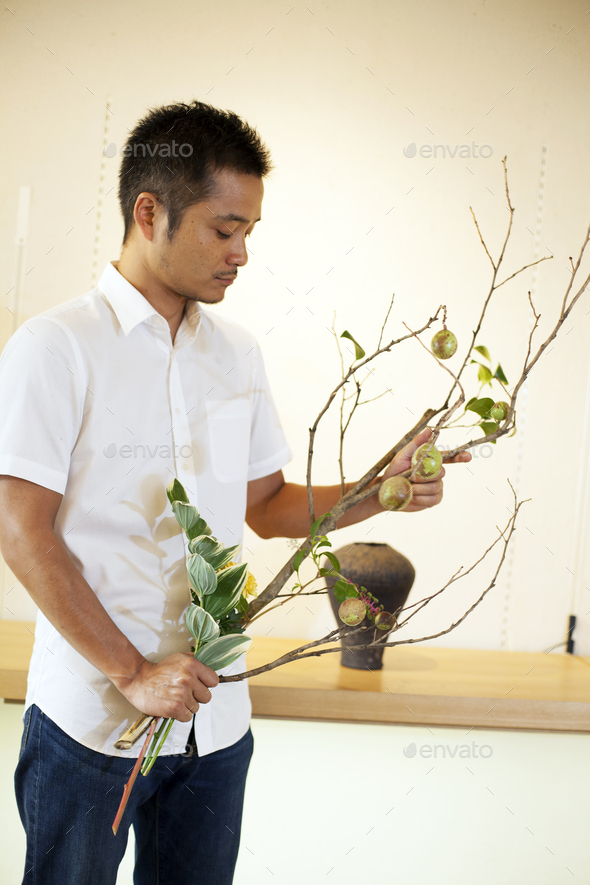 Japanese man standing in flower gallery, working on Ikebana arrangement. - Stock Photo - Images