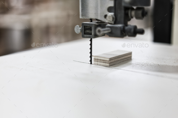 A close up of a band saw used to cut small pieces of wood in a cabinet shop. - Stock Photo - Images