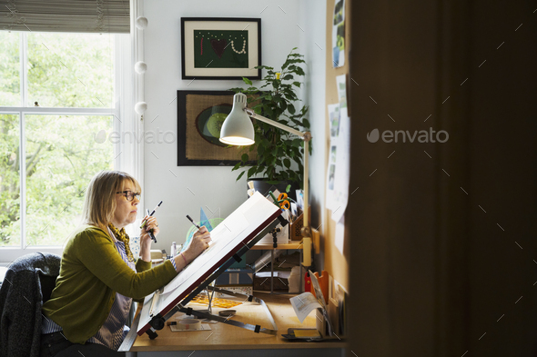 Woman sitting at a drawing board, drawing with a fineliner. - Stock Photo - Images