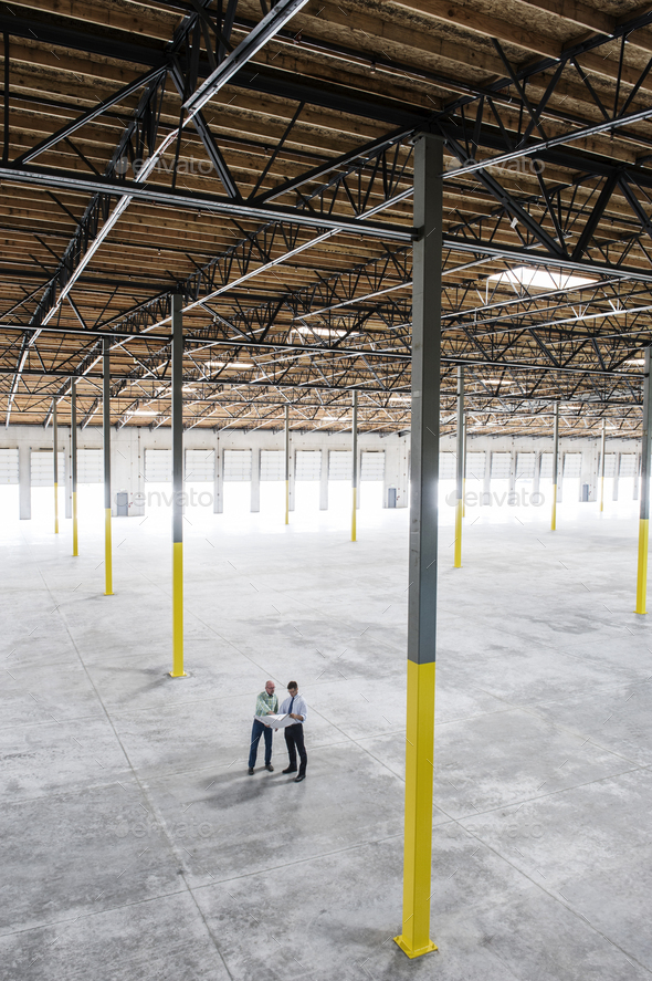 Team of people checking out the new interior of an empty warehouse space. - Stock Photo - Images