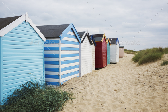 Row of colourful painted beach huts on a sandy beach under a cloudy sky. - Stock Photo - Images