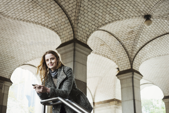A woman with long hair looking at her smart phone, under an archway. - Stock Photo - Images