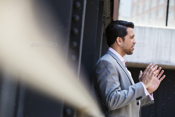 Businessman wearing a grey suit standing outdoors, talking and gesturing with his hands raised. - Stock Photo - Images