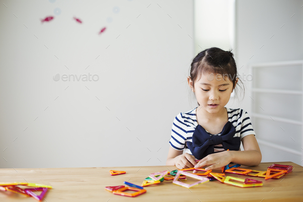 A girl sitting playing with coloured geometric shapes. - Stock Photo - Images