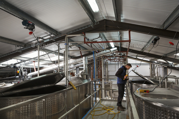 Man checking large metal tanks in a distillery or brewery, lifting the lid on a chamber full of beer - Stock Photo - Images