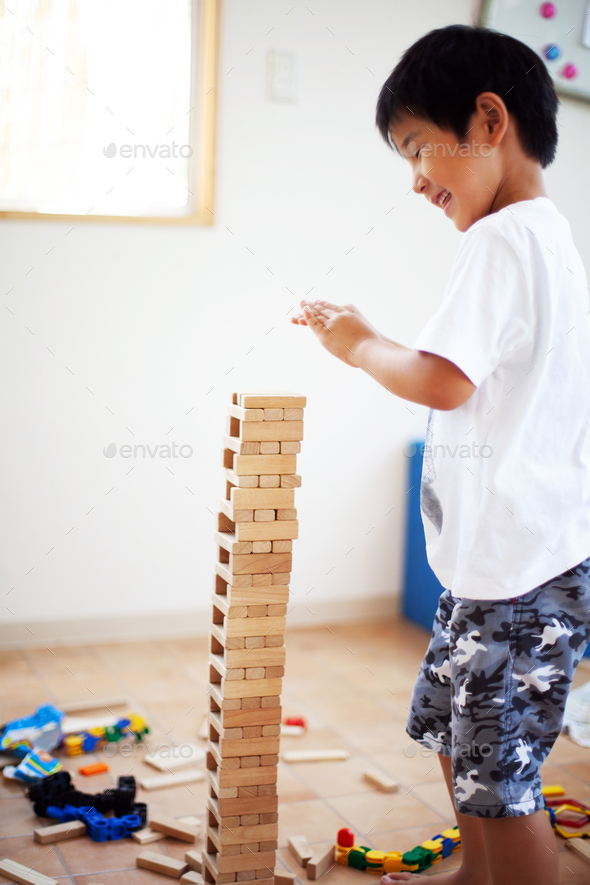 Boy playing with Jenga hardwood game in a Japanese preschool. - Stock Photo - Images