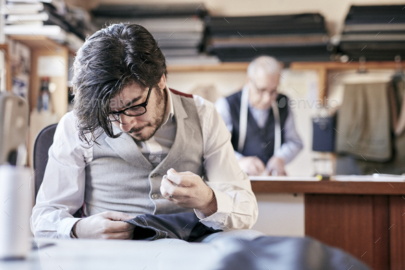 Tailor with measuring tape around neck working with material at bench - Stock Photo - Images