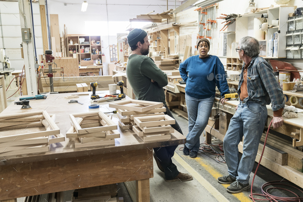 A group of mixed race carpenters discussing a project at a work station in a large woodworking shop. - Stock Photo - Images
