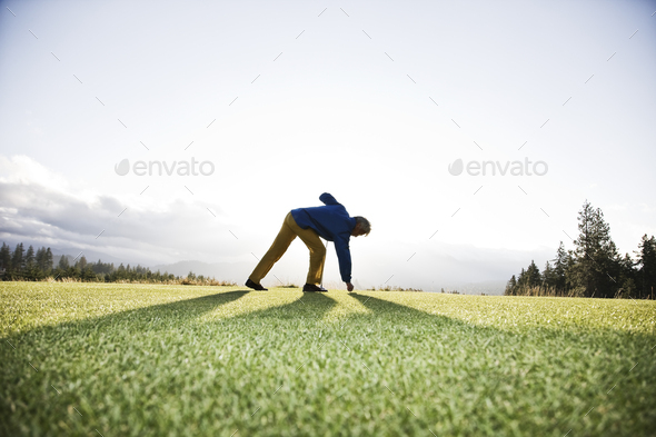 An asian senior man teeing up a golf ball and ready to swing. - Stock Photo - Images