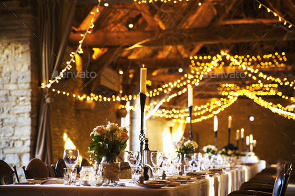 A wedding venue decorated for a party, with fairy lights and the tables set for dinner. - Stock Photo - Images