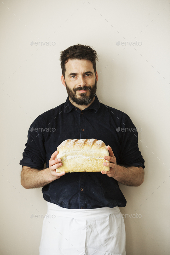 Baker holding a loaf of freshly baked white bread. - Stock Photo - Images