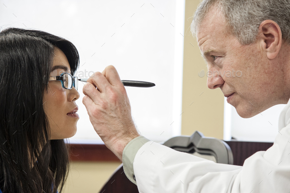 Caucasian male ophthalmologist working with an asian woman who is purchasing a new pair of glasses. - Stock Photo - Images