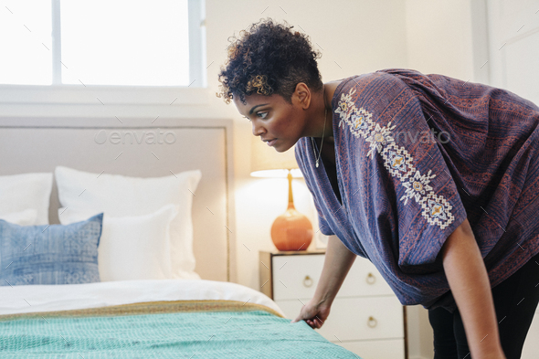 A woman smothing a throw over a double bed in a bedroom. - Stock Photo - Images