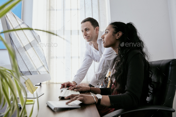 Man standing by a woman looking at a computer screen, - Stock Photo - Images