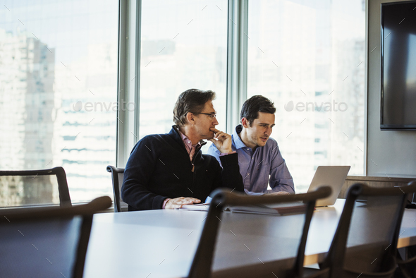 Two men at a table in a meeting room looking at a laptop computer. - Stock Photo - Images
