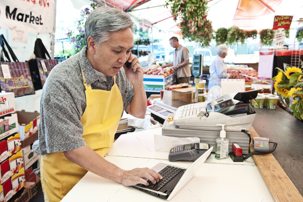 Man wearing apron standing at the checkout of a food and vegetable market, on the phone, typing on - Stock Photo - Images