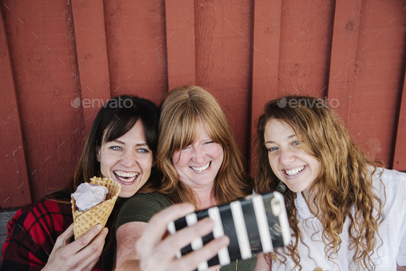 Three women eating ice cream, taking a selfie with a cell phone. - Stock Photo - Images