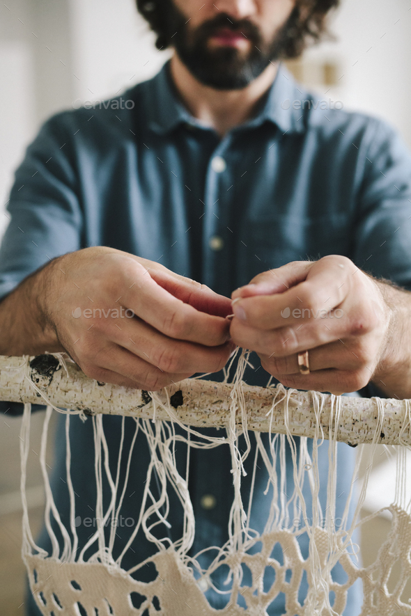 An artist working on an art piece hanging on a frame, knotting and weaving threads. - Stock Photo - Images